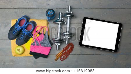 Colorful Fitness Equipment And Blank Digital Tablet On Gym Floor