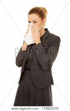 Business woman with an allergy or cold sneezing into tissue