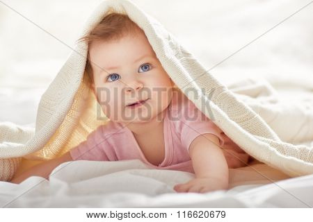 Beautiful smiling cute baby girl on the bed in the room. Happy child laughing.
