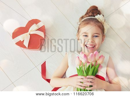 Sweet child girl with red heart and bouquet of tulips. Happy little girl with Valentine's gift lying on white wooden floor. Wedding, Valentine concept.