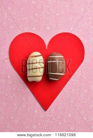 Brown and white date chocolate placed on a red color heart-shaped card.