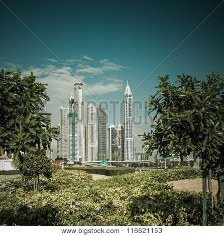 Swanky skyline of Dubai. View from a green urban landscape.