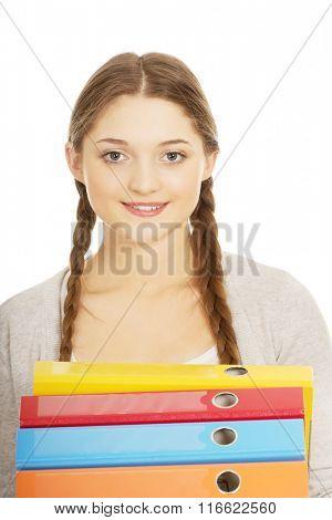 Teen woman holding binders.