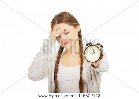 Tired teenage woman with alarmclock.