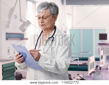 Old female doctor writing notes on clipboard at hospital room,