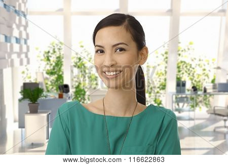 Portrait of happy casual asian businesswoman at office. Looking at camera, smiling. Copyspace.