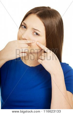 Young woman squeezing pimple.