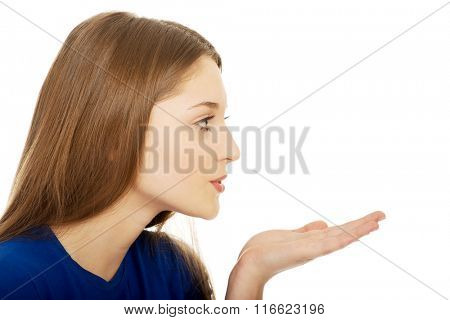 Beautiful young woman blowing a kiss.