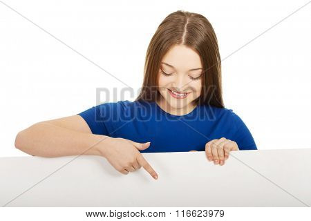 Happy woman pointing on blank board.