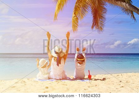 mother with two kids hands up on the beach