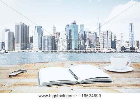 Blank Open Diary With Cup Of Coffee And Eyeglasses On Wooden Table In Front Of Financial District