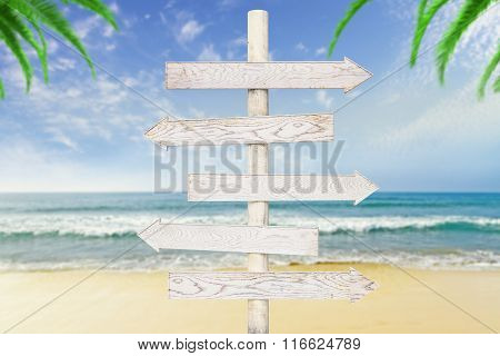 White Wooden Arrows-pointers At Ocean With Beach Background