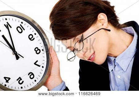 Tired business woman holding clock in hands.