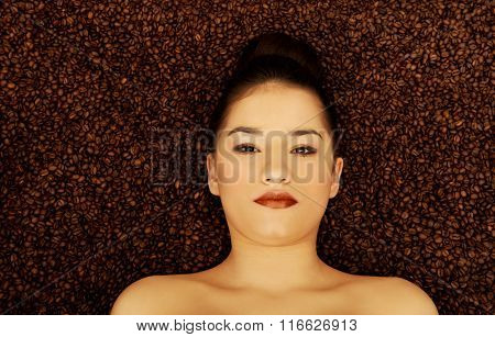 Attractive woman lying in coffee grains.
