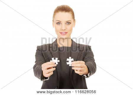 Businesswoman holding two puzzles.