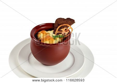 Side view of roasted  beef meat with vegetables and herbs  in round ceramic pot on  plate isolated w