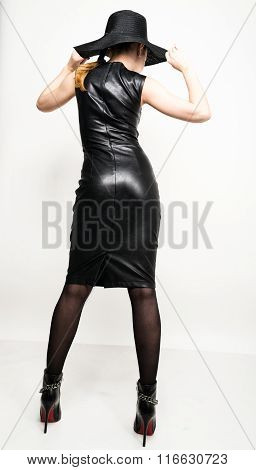 sexy young woman in black leather dress with braided hair. a big black hat on his head