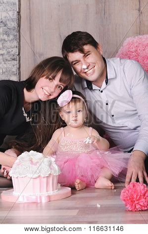 Happy family - mother, father and daughter celebrating first birthday with cake, all of them with smeared in cream faces