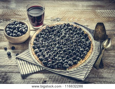 Tart with blueberries and juice on a wooden background.