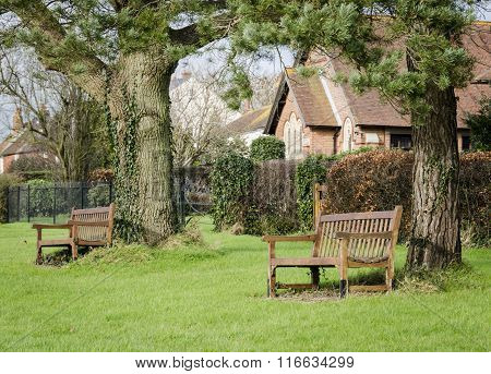 Benches Under Trees On A Village Green In Kent
