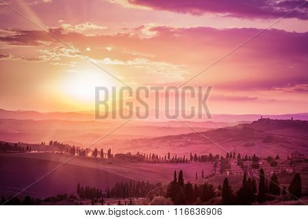 Wonderful Tuscany countryside landscape with cypress trees, farms and small medieval towns, Italy. Pink and purple sunset