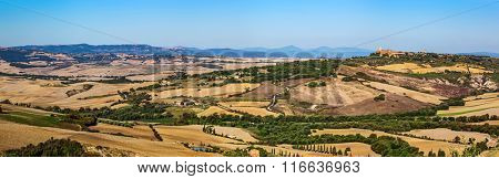 Tuscany landscape panorama with Pienza town on the hill, Italy. Cypress tree on the typical white road.