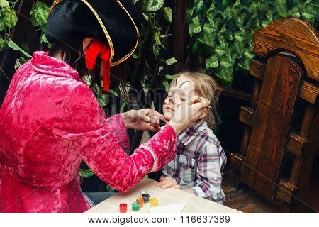 Woman Paints Face Of A Girl