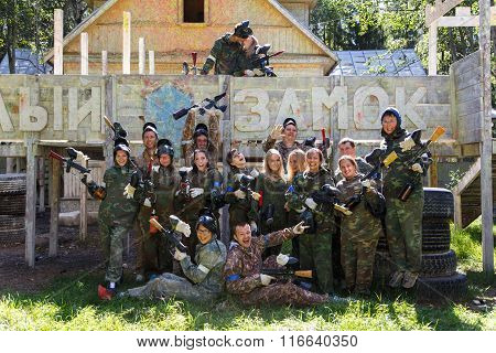Big Company Of Paintball Players And Kissing Couple On Background