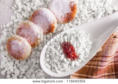 Cheesecakes with powdered sugar, cottage cheese and jam, sour cream on a background of scattered mue