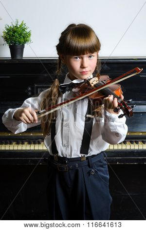 Cute little girl playing violin and exercising indoor