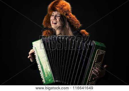 attractive emotional woman in fur hat playing the accordion