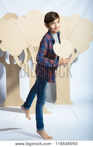 Lover Boy holding a cardboard heart. Love concept