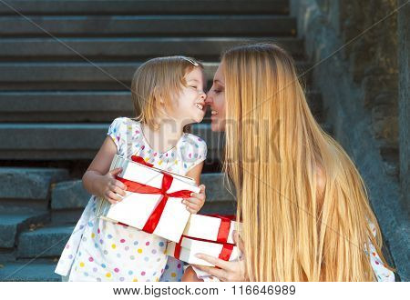 Cute Little Girl And Her Mother Holding Presents