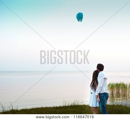 Young Couple Start A Green Chinese Sky Lantern In The Dusk