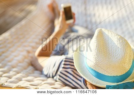 Man In Hat In A Hammock With Mobile Phone On A Summer Day