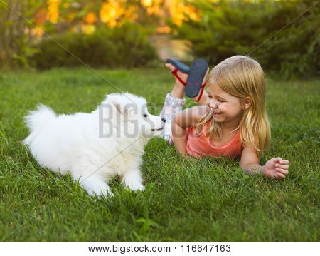 Little Smiling Girl Playing With Samoyed Puppy In The Summer Garden