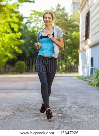 Young Female Runner In Hoody Is Jogging In The City