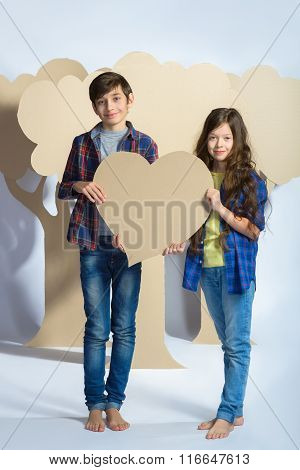 Boy and girl holding a cardboard heart. Love concept