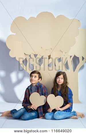 boy and girl keep hearts sit under cardboard tree. Love concept