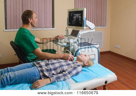 girl getting ultrasound of a thyroid from doctor