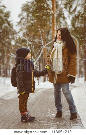 Happy family in winter clothing. Little boy holding the hand of his mother