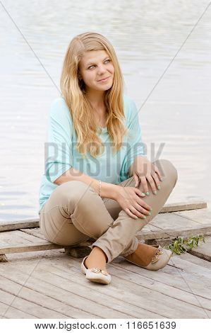Young blonde woman by the riverside.