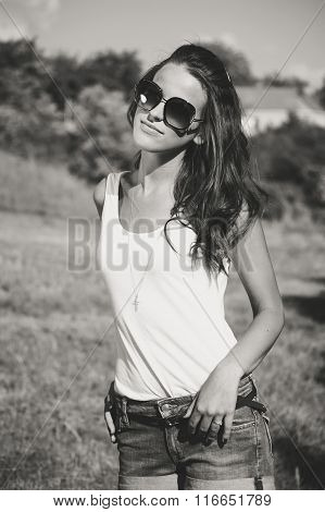 Beautiful sexy woman on the nature background in sunglasses