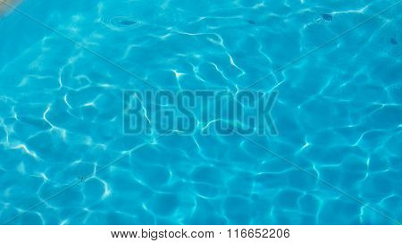 pattern of water of swimming pool with light in it and pool's stairway, a lot of space for text over blue water with play of light and shadow on pools bottom