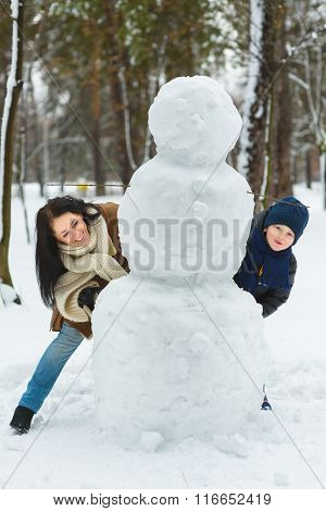 Happy family in warm clothing. Smiling mother and son standing next to a snowman outdoor. The concep