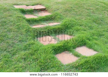 The Stone Path Through On Green Grass In The Garden.