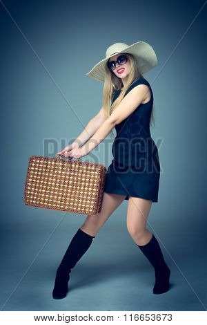 The traveler woman standing with retro suitcase