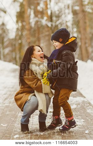 Happy family in winter clothing. Smiling mother and son outdoor