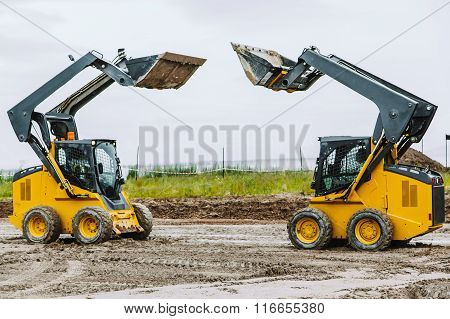 two skid steers with raiced bucket outdoors