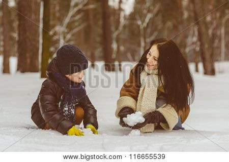 Happy family in warm clothing. Smiling mother and son playing fun game outdoor. The concept of winte